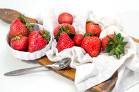 Strawberries on board cutting on striped napkin